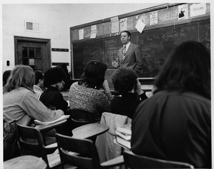 MSU President Clifton Wharton stands at the front of a classroom speaking to a large group of students.