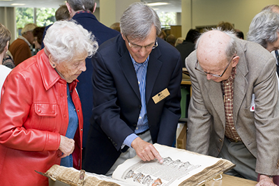 Library guests examine a copy of the famous Nuremberg Chronicle with Peter Berg, head of Special Collections.