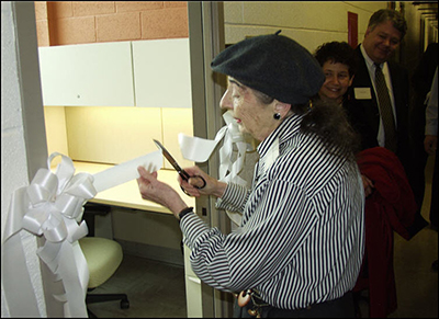 Mrs. Selma Hollander cutting a white ribbon