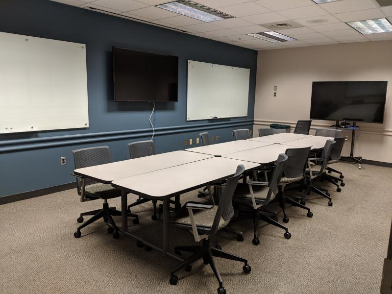 6 movable tables with about 10 wheeled chairs, 2 large monitors, and two whiteboard on wall