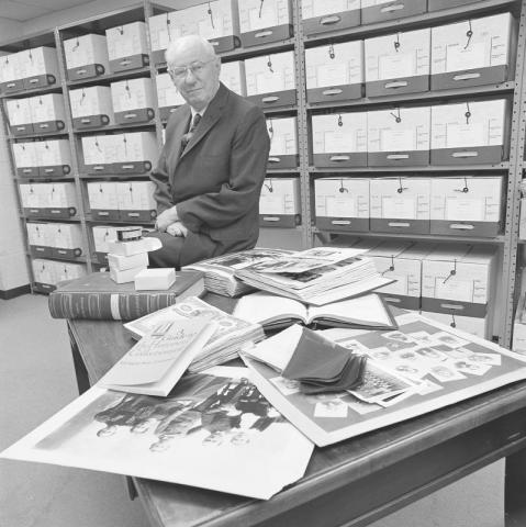Dean William Combs, first director of the MSU Archives, poses with archival materials.