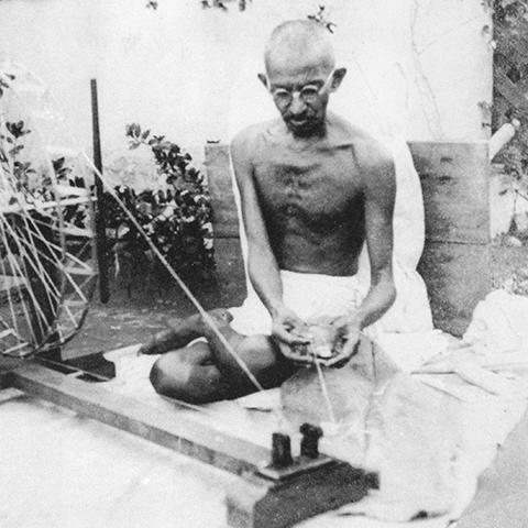 Gandhi, seated, with food