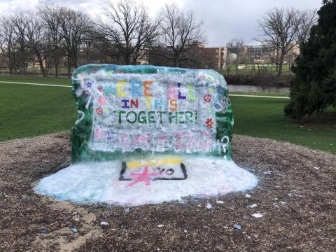 "Photo of The Rock at MSU with ""we're all in this together!"" painted on it."