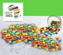 Jar spilling candies in the shape of Africa