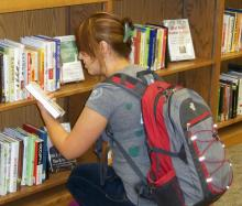 student looking at books on shelf